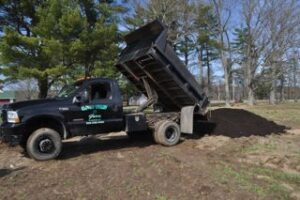 A black truck dumps a pile of compost in a dirt field at the farm